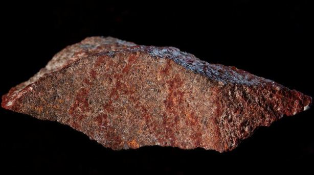 Lukisan berupa garis-garis silang pada batu dengan pigmen merah oker itu diperkirakan berumur sekitar 73.000 tahun. (Foto: Reuters)