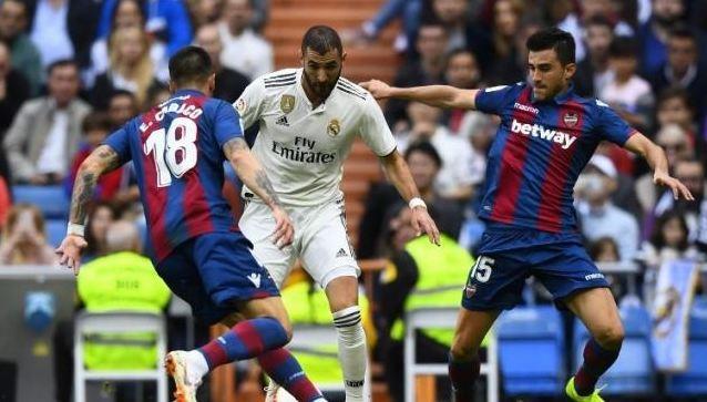Pemain depan Real Madrid Karim Benzema (tengah) mencoba melewati dua pemain Levante Erick Cabaco (kiri) dan Sergio Postigo di Santiago Bernabeu.