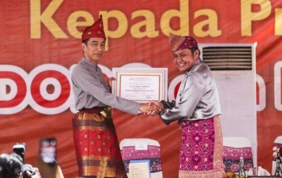 Presiden Joko Widodo (kiri) menerima piagam gelar adat kehormatan dari Gubernur Sumatera Selatan Herman Deru (kanan) saat penganugerahan gelar kehormatan adat Komering Provinsi Sumatera Selatan di halaman Griya Agung Palembang, Sumatera Selatan, Minggu (25/11/2018).
