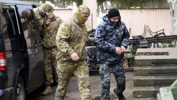 Seorang tentara Angkatan Laut Ukraina yang ditangkap (kanan), dikawal oleh petugas intelijen Rusia di Simferopol, Krimea, Selasa (27/11).
