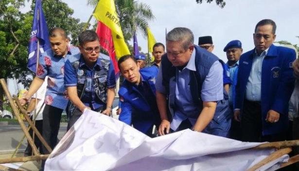 SBY saat membenahi balihonya yang dirusak orang tak dikenal.