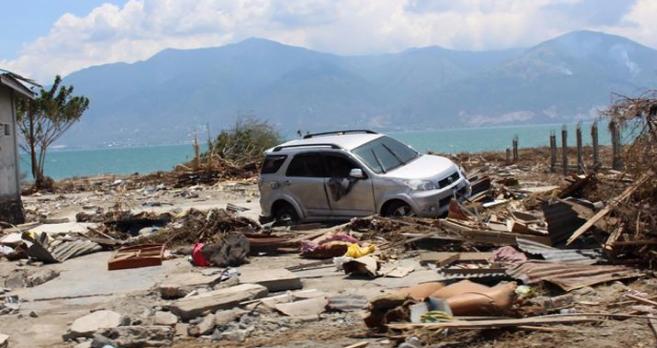 Sebuah mobil dan puing-puing bangunan yang hancur usai diguncang gempa dan tsunami.