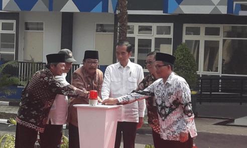 Jokowi menekan sirine tanda peresmian rusunawa.