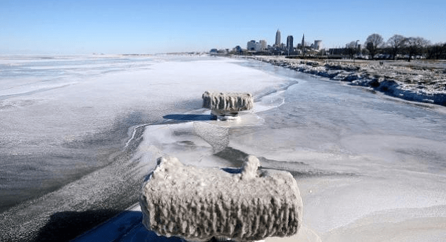 """Pemandangan es menutupi garis pantai Danau Erie dengan garis langit Cleveland di belakang saat fenomena """"polar vortex"""" di Cleveland, Ohio, Amerika Serikat, Kamis (31/1/2019)."""
