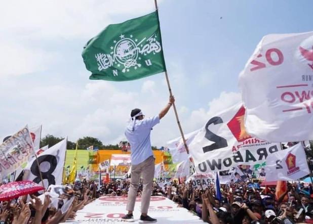 Sandiaga mengibarkan bendera NU saat berkampanye di Lumajang. (Istimewa)