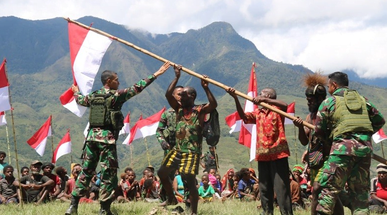 Warga Kampung Yunggwi, Distrik Wanwi, Kabupaten Puncak Jaya, Papua, mengibarkan bendera Merah Putih bersama Satgas Yonif MR 412/BES Kostrad. (Foto: Dispenad)