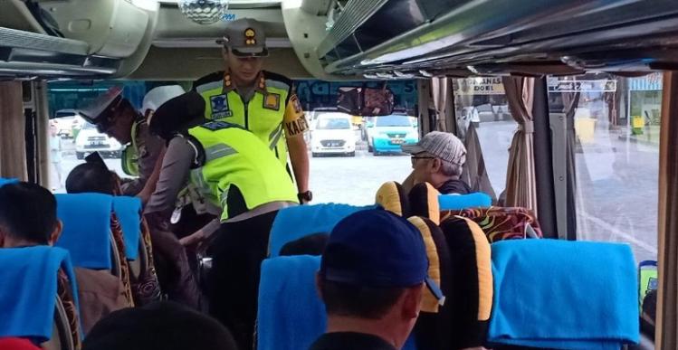 Polisi saat  Sweeping penumpang bis di Rest Area Tol Madiun.