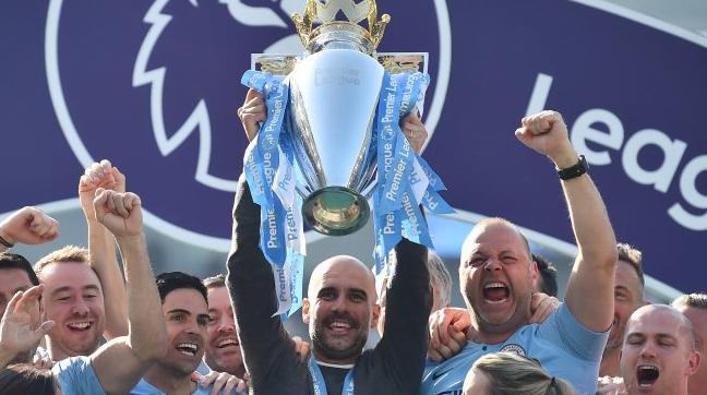 Manajer Manchester City Pep Guardiola mengangkat trofi juara Premier League setelah skuatnya mengalahkan Brighton and Hove Albion di pekan terakhir Liga Inggris. Glyn KIRK / AFP