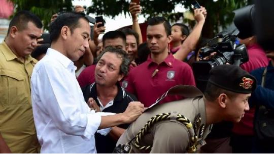 Jokowi meminjam punggung ajudan. (Foto: Biro Pers Setpres)