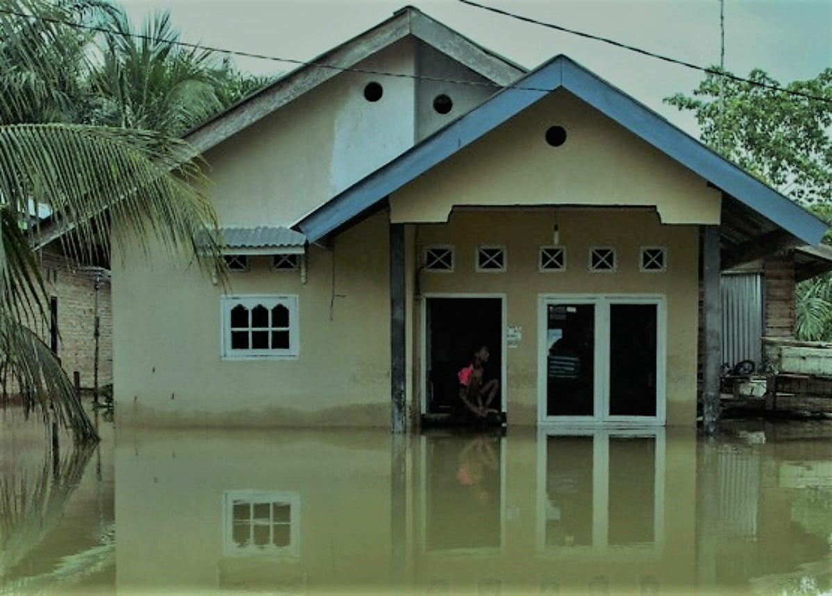 Warga duduk di depan pintu rumahnya yang terendam banjir luapan Sungai Kampar di Desa Buluhcina, Kabupaten Kampar, Riau, Rabu (18/12/2019). Tingginya curah hujan membuat Sungai Kampar meluap dan merendam sejumlah desa di sepanjang aliran sungai tersebut. ANTARA FOTO/Rony Muharrman/wsj.